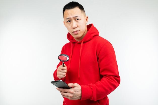 De donkerbruine kerel in een rode sweater bekijkt de telefoon door een vergrootglas op een witte achtergrond