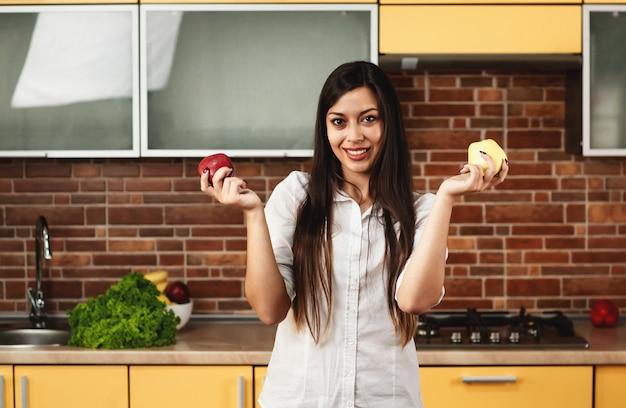 De donkerbruine vrouw houdt rode en gele appelen in haar handen. een vrouw die zich in de keuken bevindt en welke te eten appel kiest. vrouw die camera bekijkt. het concept van voeding en gezond eten