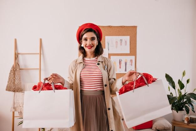 De donkerbruine vrouw in rode hoed onderzoekt camera en houdt boodschappentassen. leuk mooi meisje in stijlvolle herfst jurk poseren in appartement.