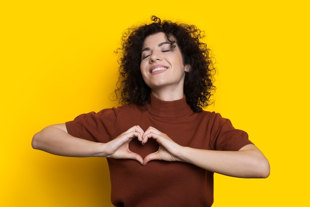 De donkerbruine vrouw met krullend haar gebaart het liefdeteken met haar handen die op een gele studiomuur glimlachen