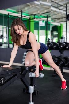 De donkerbruine vrouw met sterk geschikt lichaam doet verschillende oefeningen in moderne sportkleding