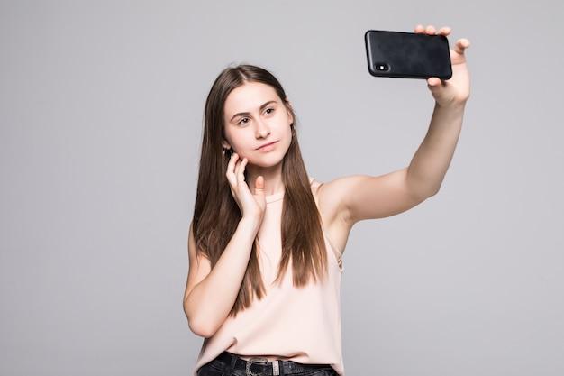 De donkerbruine vrouw neemt selfie met slimme telefoon die op wit wordt geïsoleerd