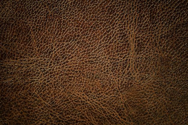 De donkere bruine achtergrond van de leertextuur, close-up. bronzen gebarsten achtergrond van rimpelhuid