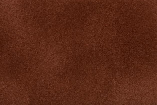 De donkere bruine close-up van de suèdestof. fluwelen textuur.