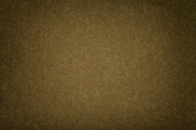 De donkere bruine matte close-up van de suèdestof. fluwelen textuur van vilt.