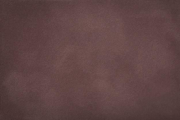 De donkere bruine matte close-up van de suèdestof. fluwelen textuur.