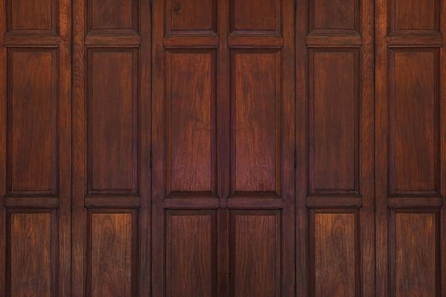 De donkere bruine oude oude houten achtergrond van de schommeldeur. thailand traditionele stijl. gebruiken als muur of behang.