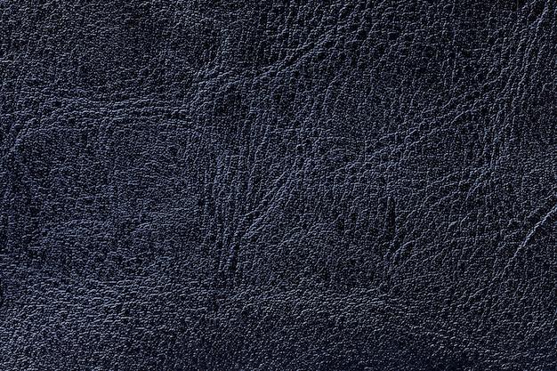 De donkere marineblauwe achtergrond van de leertextuur, close-up
