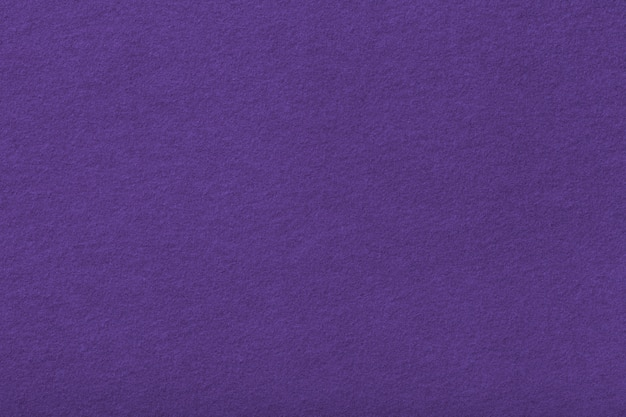 De donkere purpere matte close-up van de suèdestof. fluwelen textuur van vilt achtergrond