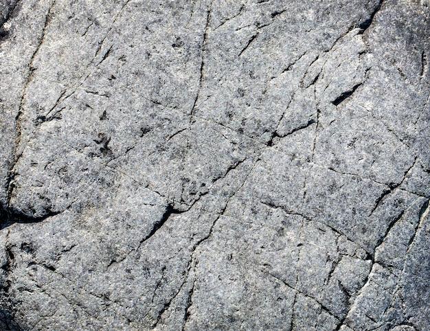 De donkergrijze zwarte stenen achtergrond of textuur.