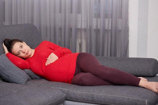 De donkerharige aantrekkelijke toekomstige moeder ligt op een comfortabele grijze bank, gekleed in een warme, felrode trui en een kastanjebruine legging