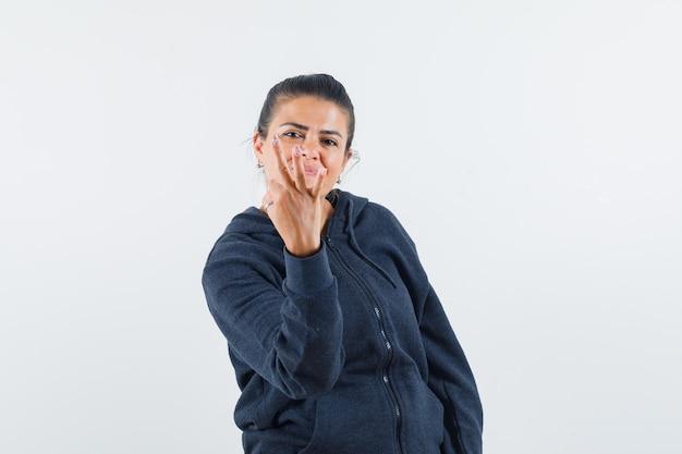 De donkerharige vrouw die ok gebaar met omgekeerde toont dient jasje in en kijkt tevreden. vooraanzicht.