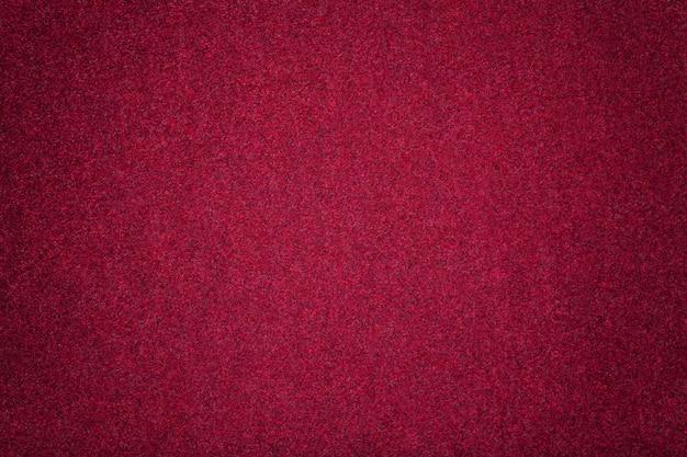 De donkerrode matte close-up van de suèdestof. fluwelen textuur van vilt.