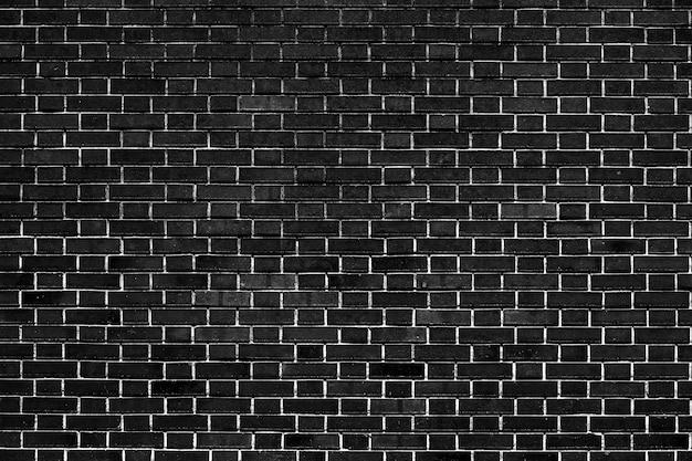 De donkerzwarte bakstenen muur heeft een ruw oppervlak als achtergrondafbeelding.