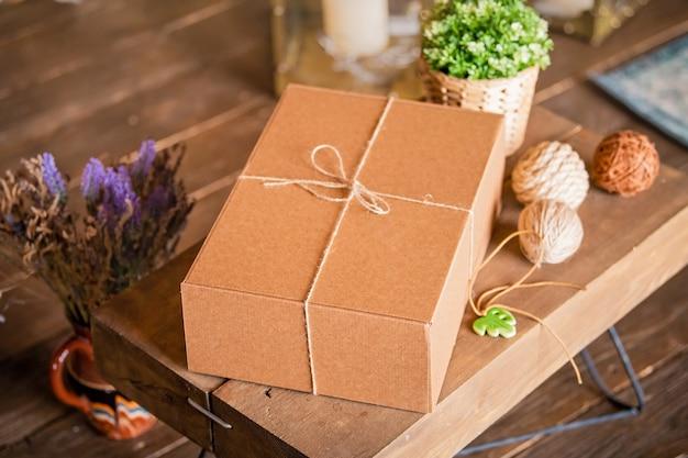De doos is gemaakt van bruin karton, vastgebonden met een touw. handgemaakt cadeau.