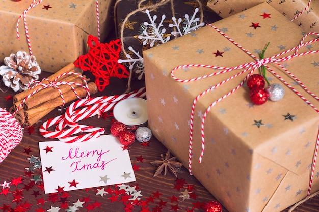 De doos van de de vakantiegift van kerstmis met prentbriefkaar vrolijke kerstmis op verfraaide feestelijke lijst met denneappelskaneel