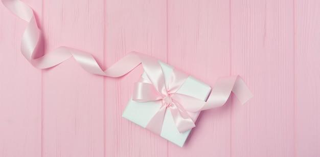 De doos van de gift van de banner met lint op roze houten achtergrond met plaats voor uw tekst