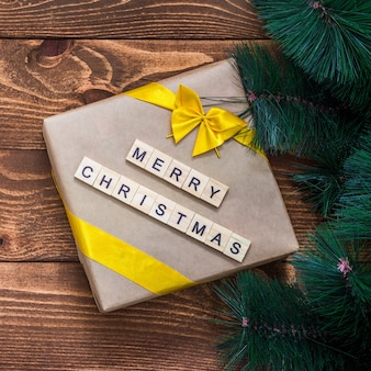 De doos van de gift van kerstmis en boomtak decor op houten tafel met merry christmas-tekst. plat leggen