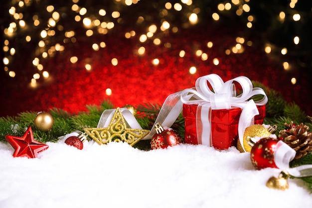 De doos van de gift van kerstmis en decoratie in de sneeuw met bokeh lichten
