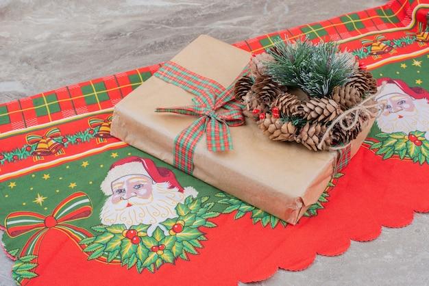 De doos van de gift van kerstmis en krans met dennenappel op marmer.
