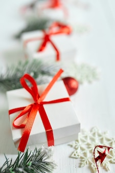 De doos van de gift van kerstmis, fir boomtakken, rode decoraties op witte houten tafel