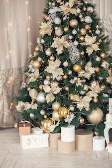 De doos van de gift van kerstmis ligt op de vloer onder de kerstboom versierd met gouden speelgoedballen en slingers