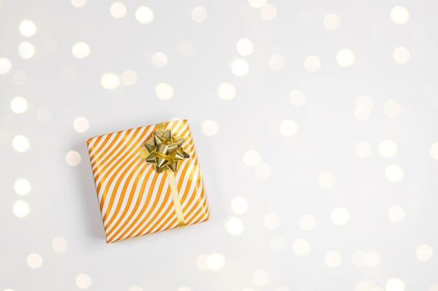 De doos van de gift van kerstmis met gouden strik, gouden confetti lichten