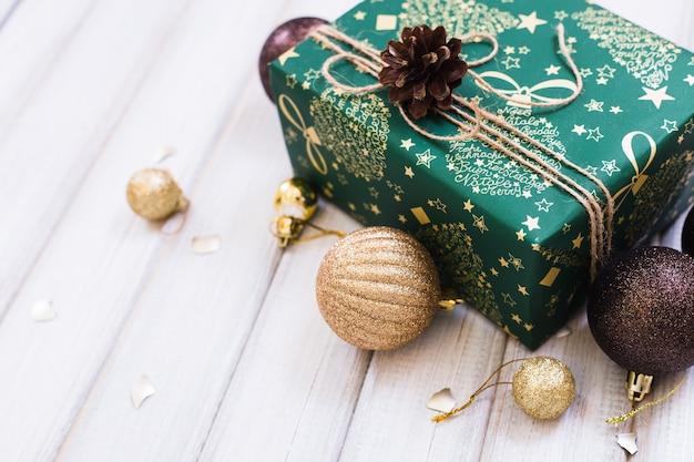 De doos van de gift van kerstmis met lint boog en bal speelgoed op witte houten achtergrond