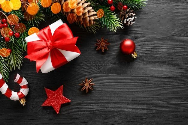 De doos van de gift van kerstmis met rode strik en decoraties op zwarte houten tafel, bovenaanzicht, plat leggen