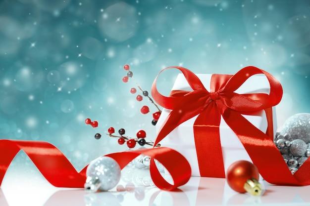 De doos van de gift van kerstmis met rode strik op blauwe lichten