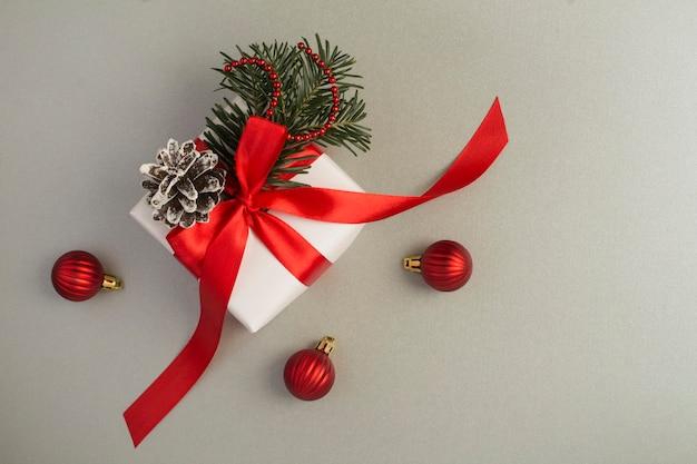 De doos van de gift van kerstmis met rood lint op de grijze achtergrond. bovenaanzicht. ruimte kopiëren.