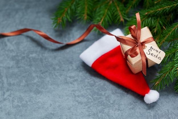 De doos van de gift van kerstmis met tag en kerstmuts op achtergrond