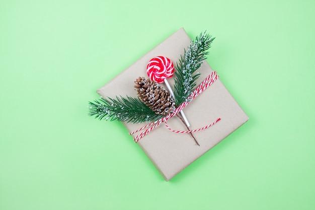 De doos van de gift van kerstmis verpakt in bruin ambachtelijk papier met maïs, dennenboom en snoep op groene achtergrond. kerst concept. eco-pakket. focus op maïs