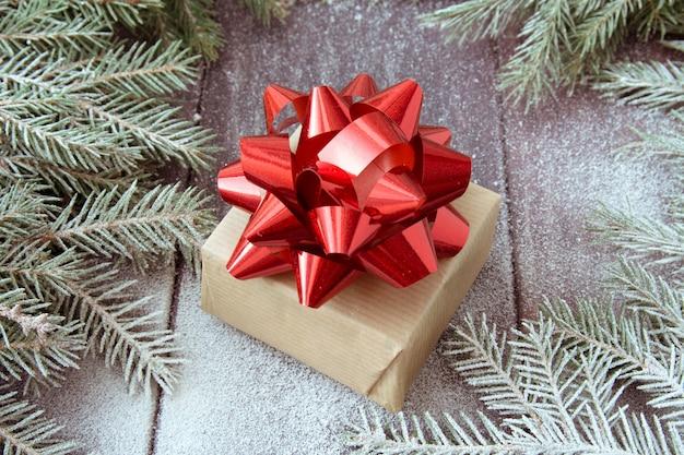 De doos van de gift van kerstmis verpakt in kraftpapier met rood lint op sneeuw bedekt donkere houten achtergrond