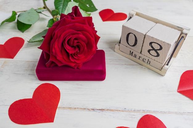 De doos van de juwelengift met en mooie rode rozen op houten achtergrond. wenskaart voor 8 maart.