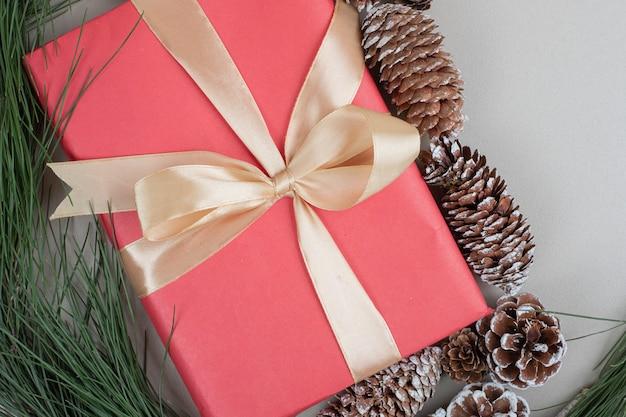 De doos van de kerstmisgift die met lint en dennenappels wordt gebonden