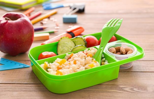 De doos van de lunch van de school met lekker eten op houten achtergrond