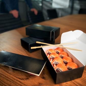 De doos van de sushibroodje op werkruimte met eetstokjes. lunch op kantoor