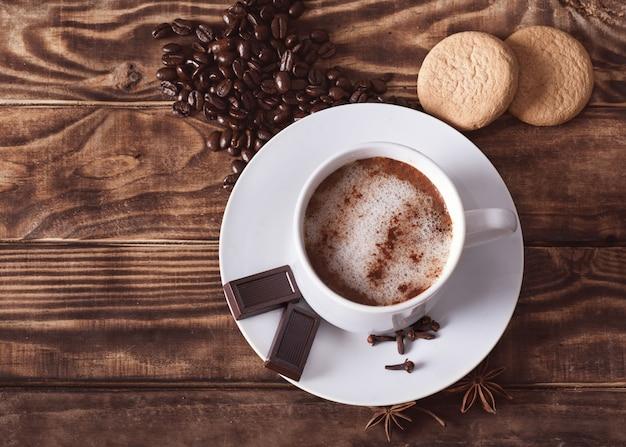 De dop van koffie met schuim, chocolade, gebak, hartvormige koffiebonen op de houten tafel