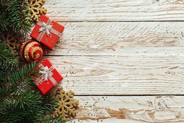 De dozen van de kerstmisgift op houten witte achtergrond. kerstmis en gelukkig nieuwjaar samenstelling. bovenaanzicht