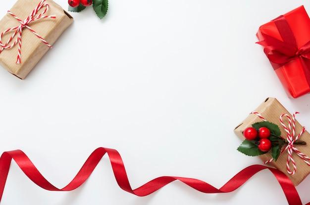 De dozen van de kerstmisgift, rood lint dat op witte achtergrond wordt geïsoleerd.
