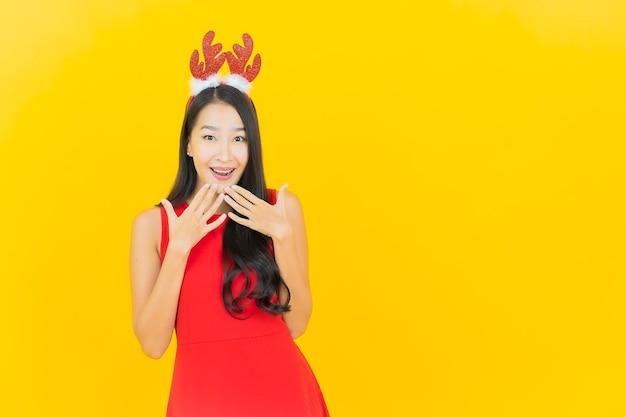 De draag santahoed of haarband van de portret mooie jonge aziatische vrouw op gele muur