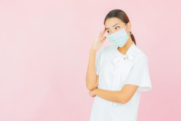 De draagmasker van de portret mooi jong aziatisch vrouw voor beschermt covid19 op roze muur