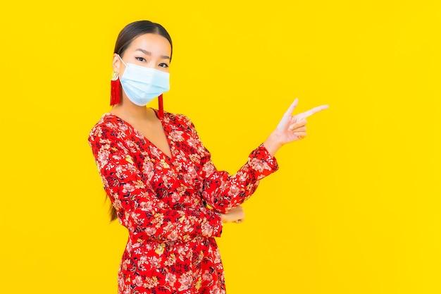 De draagmasker van de portret mooi jonge aziatische vrouw voor beschermt coronavirus of covid19 op gele muur