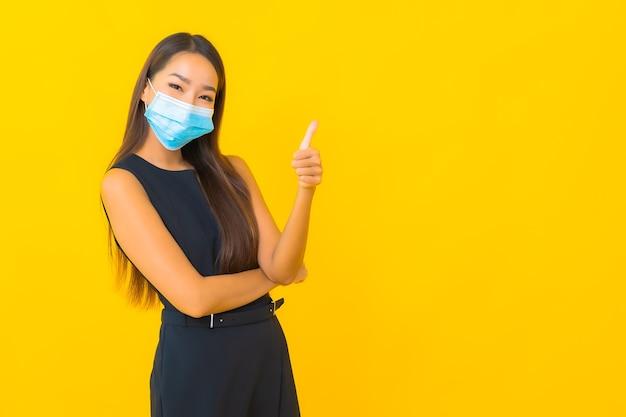 De draagmasker van het portret mooi jong aziatisch bedrijfsvrouw voor beschermt covid19 op gele achtergrond