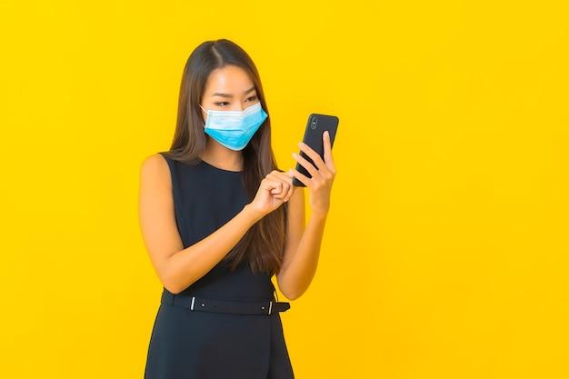 De draagmasker van het portret mooi jonge aziatische bedrijfsvrouw voor beschermt covid19 en gebruikt mobiele telefoon
