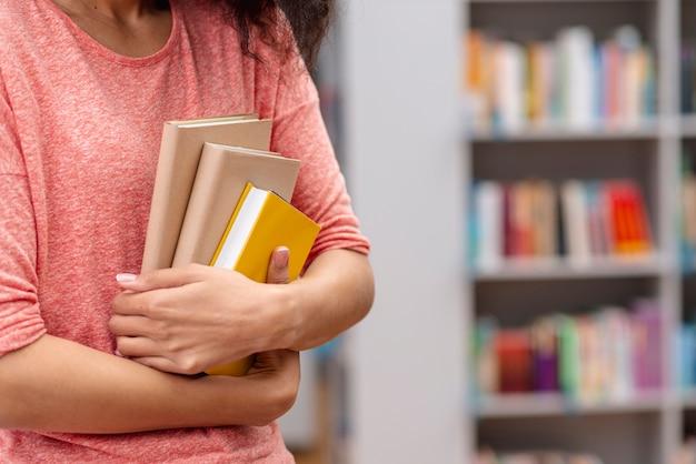 De dragende stapel boeken van het close-upmeisje