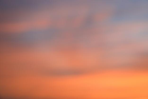 De dramatische achtergrond van de zonsonderganghemel met vurige wolken, gele, oranje en roze kleur, aardachtergrond. onscherpe achtergrond