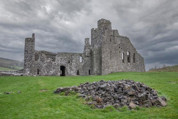 De dramatische hemel boven fore abbey met een hoop stenen op de voorgrond