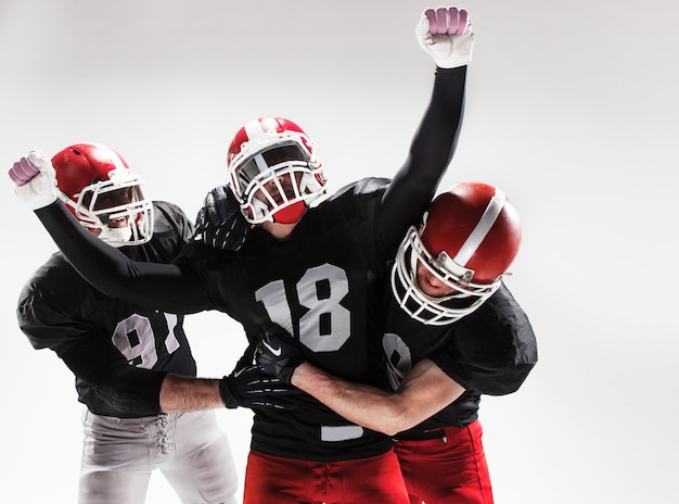 De drie amerikaanse voetballers poseren op witte ruimte